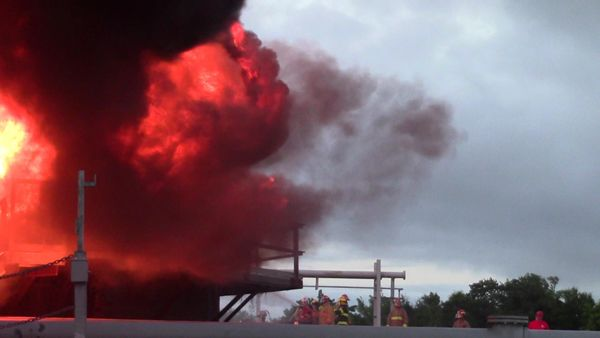 Firefighters direct foam onto a full-surface tank fire demonstration. -