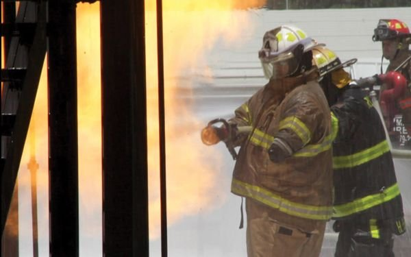 Campbell manages the nozzle during Xtreme fire school training at Brayton in June. - Photo by Anton Riecher