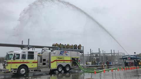 Firefighters observe a firefighting monitor demonstration.