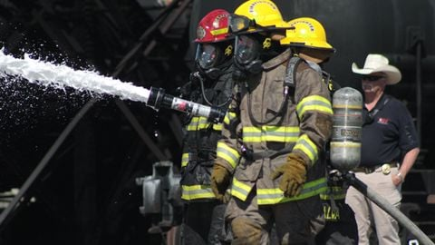 Jason Dyer, red helmet, directs a foam attack on the burning tanks at TEEX.