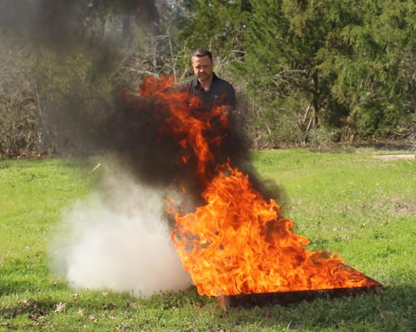 Bill Gough conducting live-fire test with the Oval extinguisher. - Photo by Anton Riecher.