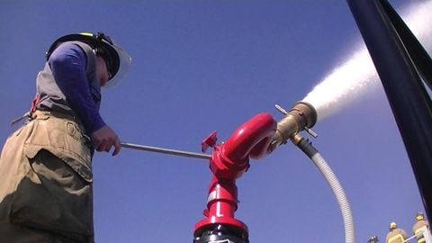 A firefighter uses a monitor to help extinguish the tank.