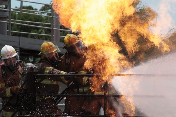 Paquin's hose team tackles a live-fire prop at TEEX. - Photo by Anton Riecher
