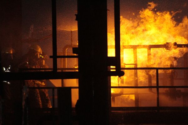 Firefighters climb the chemical process prop at night. - Photoby Anton Riecher.