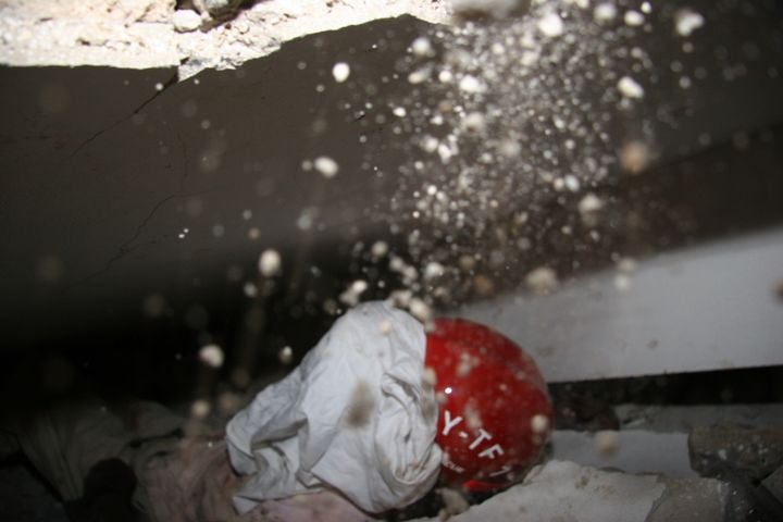 A victim of the 2010 Haiti earthquake, face covered to prevent injury, trapped in a void beneath a pancake collapse. -