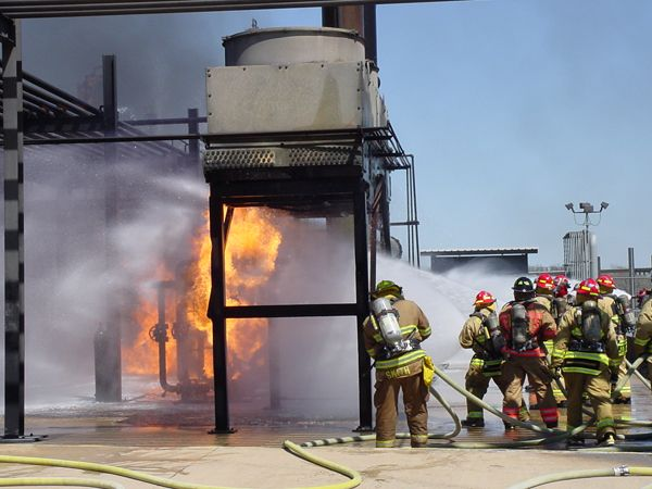 A hose team moves in on a burning pipe rack prop at the fire school. - Photo by Anton Riecher