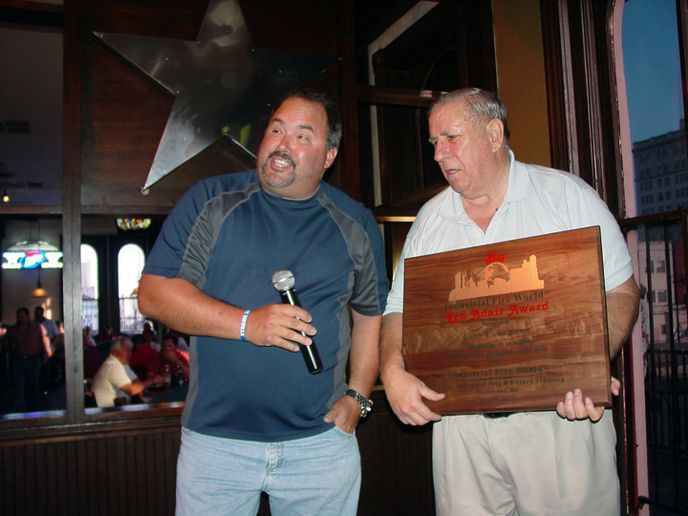 Eric LaVergne, left, business development manager for Williams Fire & Hazard Control, is presented the Red Adair award by Industrial Fire World publisher David White. -