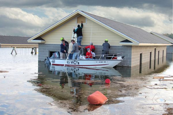 Responders use boats to access full-scale homes inundated by a simulated flood. -