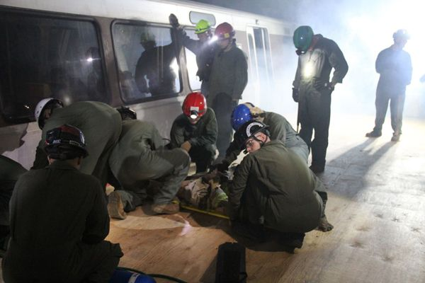 Responders train using a real commuter train in an enclosed space. -