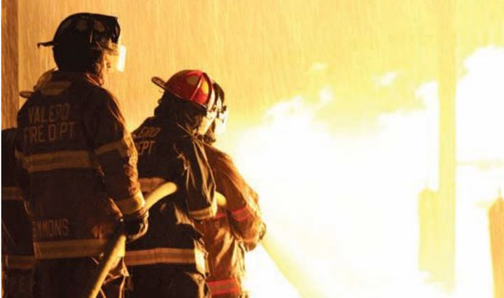 Firefighters bring a hose line to bear during night burn exercises. -
