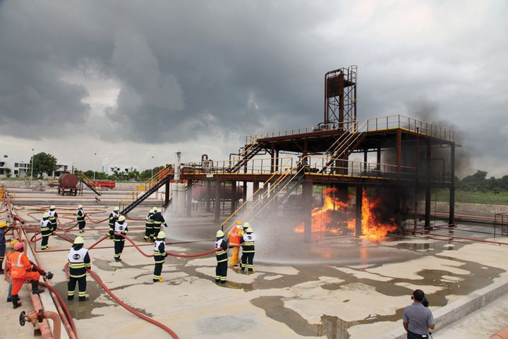 Trainees approach a prop at the Institute of Fire Safety & Disaster Management Studies that simulates a process unit fire. - Photos provided by IFSDMS