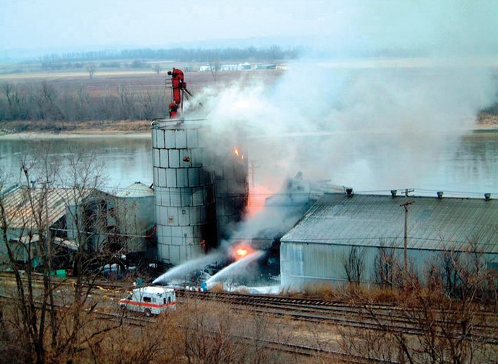 Responders battle an industrial silo fire in January 2002 at a rubber recycling plant in Nebraska City, NE. An attempt to pump nitrogen inside the silo resulted in a burst of rubber pieces and particles that showered a 350 foot area. Firefighters were struck by two-inch pieces, some with wire from shredded steel belt radials still embedded in them. Three of the 25 responders were admitted to a local hospital with injuries. - Photo by Larry Wiles