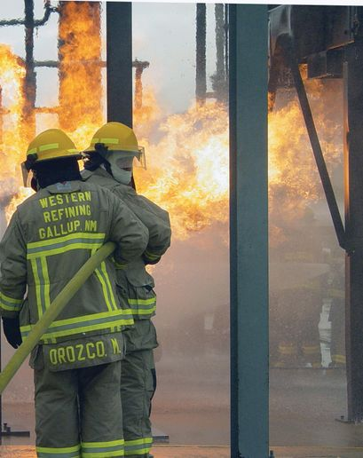 Firefighters battle flames from a pipe rack prop at TEEX fire field. -