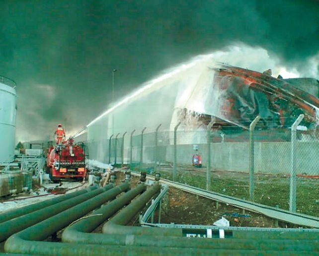 Firefighters cool the remains of a collapsed fuel storage tank at Buncefield. - Photo courtesy of Herfordshire Constabulary.