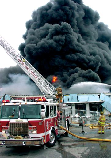 Firefighters approach a 10-story rack system warehouse. - Photo by Woody Spencer/Kinston Fire Department.