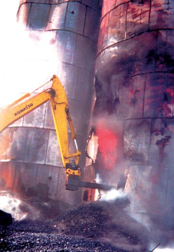 A backhoe digs into the fiery northeast silo. - Photo by Larry Wiles.
