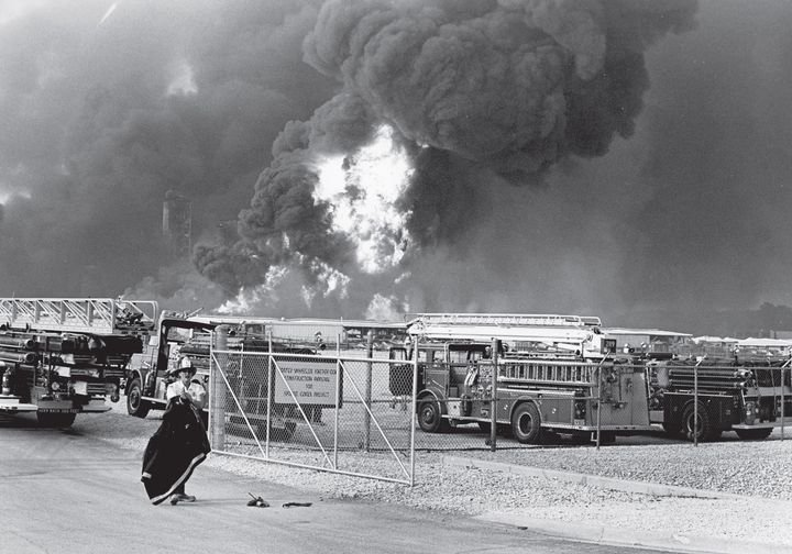 Apparatus staged near the refinery entrance as fireballs rise from the fire - Photo by John Patsch/Joliet Herald News.