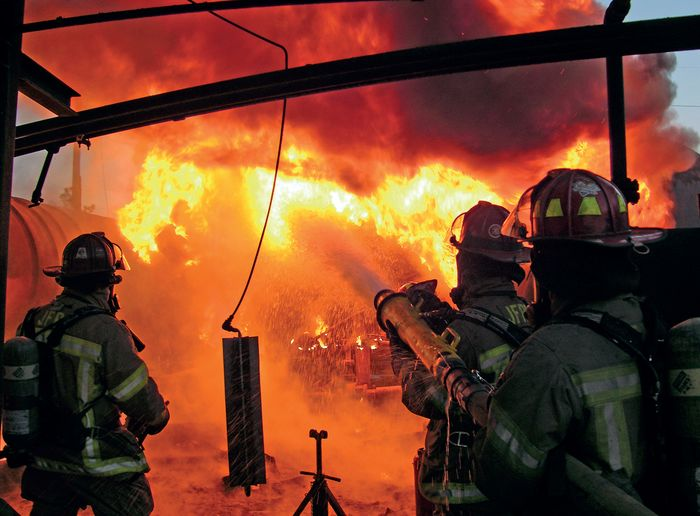 Firefighters mount a foam attack on the blazing aftermath of an industrial reactor explosion. - Photo by Mark Treglio.