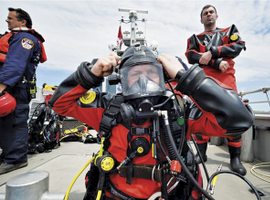 Rescue divers prepare to enter the water off of a fireboat.