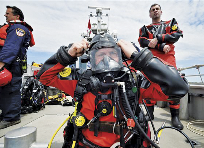 Rescue divers prepare to enter the water off of a fireboat. - Photo by James Kiesling.