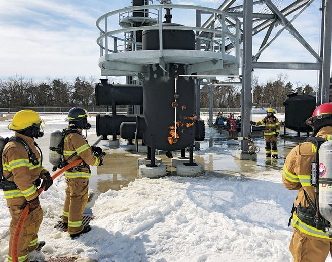 Firefighters receive additional instruction during a live-burn training exercise at the CHS fire training field in McPherson, Kansas. - Photo courtesy of CHS.