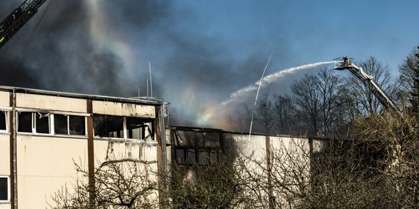 A German firefighter from Otterberg sprays water on a burning factory in Otterberg, Germany,...