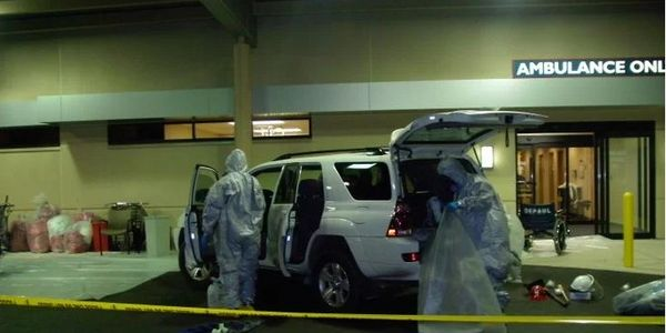 Personnel in PPE check out the vehicle that brought chemically contaminated patients to a St....