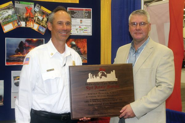 Superior, WI Fire Chief Steve Panger, left, received the 2018 Red Adair Award in August. Kollin Schade, plant manager at the Husky refinery, was on hand. - Photo by Anton Riecher.
