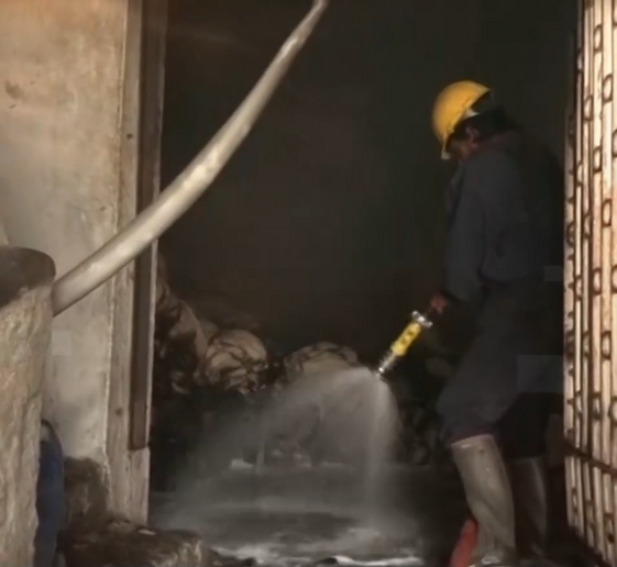 A firefighter cleans up in the aftermath of a three-hour factory fire in Pakistan Thursday - Screencapture Via GGN