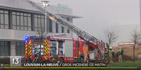 An aerial ladder is used to direct water onto the burning production hall at REALCO in Belgium.
