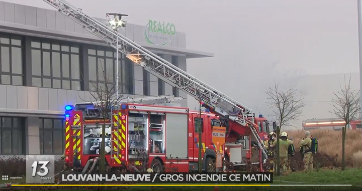 An aerial ladder is used to direct water onto the burning production hall at REALCO in Belgium. - Screen capture via RTBF