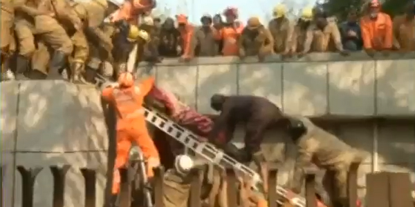 Rescuers remove victim from a collapsed building in Delhi, India.