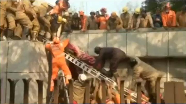 Rescuers remove victim from a collapsed building in Delhi, India. - Screencapture Via CNN
