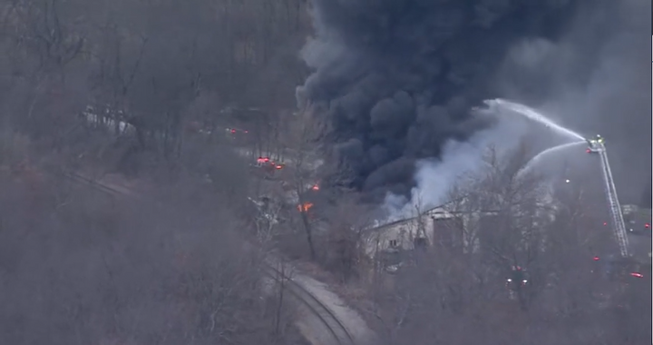 Aerials deliver water to a burning fleet maintenance garage burning after a propane blast. - Screencapture Via KDKA