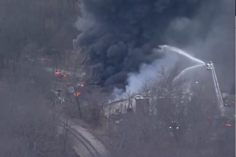 Aerials deliver water to a burning fleet maintenance garage burning after a propane blast.