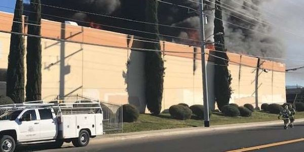 A three-alarm fire at a Banning, California, manufacturing plant sends up a tower of black smoke.