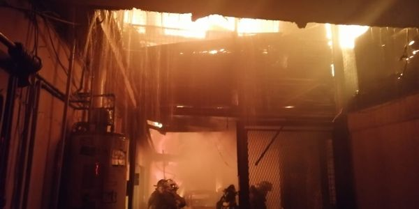 Firefighter working inside a burning furniture factory in Mexico City Monday.