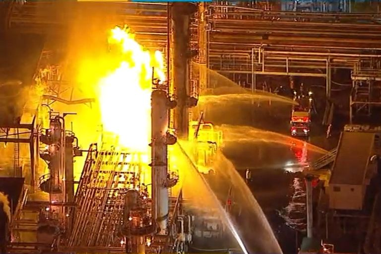 Fire trucks moved in close to the flames at the heart of the Marathon Petroleum refinery in...