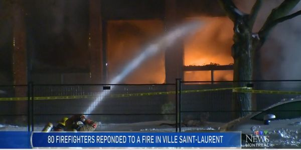 Firefighters deliver water to a burning plastics factory in Montreal Sunday evening.