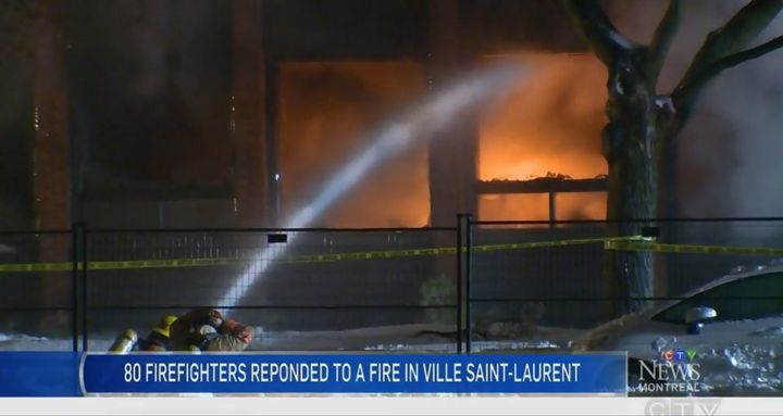 Firefighters deliver water to a burning plastics factory in Montreal Sunday evening. - Screencapture Via CTV