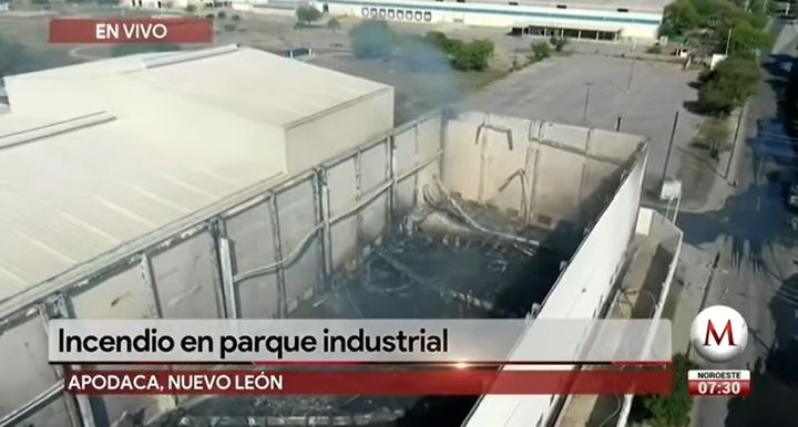 Firefighters overhaul the flame gutted interior of a warehouse in Apodaca, Mexico. - Screencapture Via Noticias Milenio