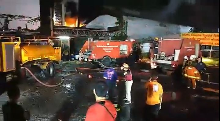 Spectators gather to watch a car paint factory fire in Bangkok, Thailand. - Screencapture Via The Nation - Thailand