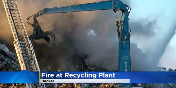 Crane digs through burning scrap pile during four-day fire in Becker, Minnesota.