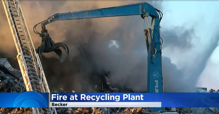 Crane digs through burning scrap pile during four-day fire in Becker, Minnesota. - Screencapture Via Twitter