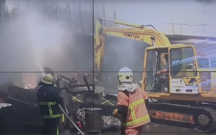 Firefighters use heavy equipment to break through the walls of a burning warehouse Thursday. - Screencapture Via Formosa TV News