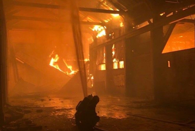 Firefighter battles flames spreading through the rafters of a warehouse in France. - Photo Courtesy of SDIS 69