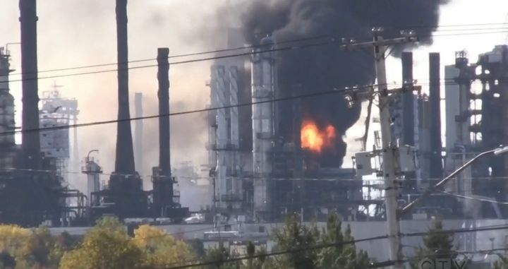 Flames shoot skyward from the interior of an oil refinery in Saint John, New Brunswick. - Screencapture Via CTV