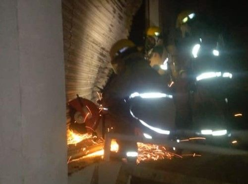 Firefighters cut their way into a burning warehouse in Apodaca, Mexico. - Photo Courtesy of Bomberos de Nuevo Leon