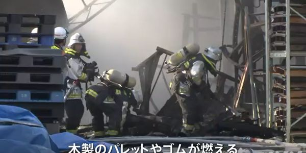 Firefighters overhaul the scene after a seven-hour blaze levelled a factory in Japan Sunday.
