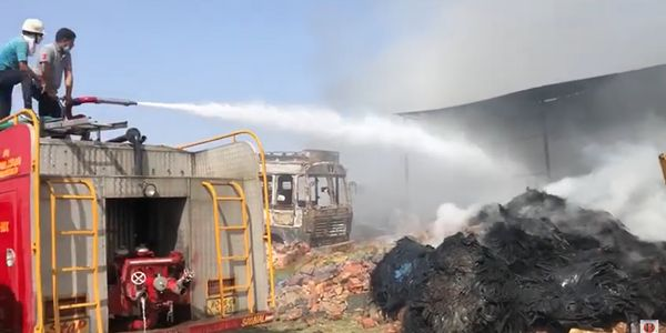 A fire truck deck gun is turned on the smoking remains of a tire recyling plant in India.